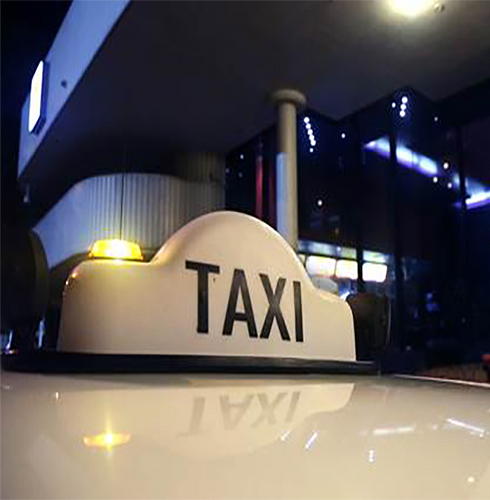 Close up of a taxi sign with lights on the top of a taxi at night