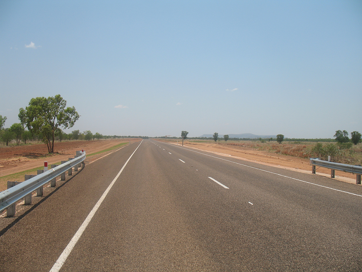 A section of the Butine Highway which has been restored. The road is clean with newly painted lines. The road is straight and the sky is clear. Dirt and several trees are either side if the road.
